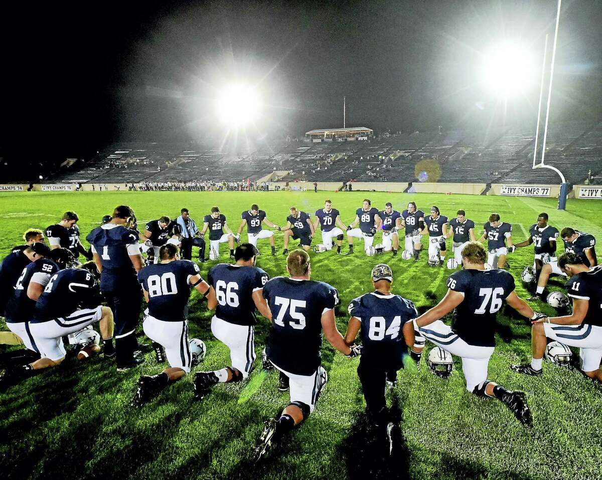 Members of the Yale football kneel for prayer before the first night football game at Yale Bowl on Friday.