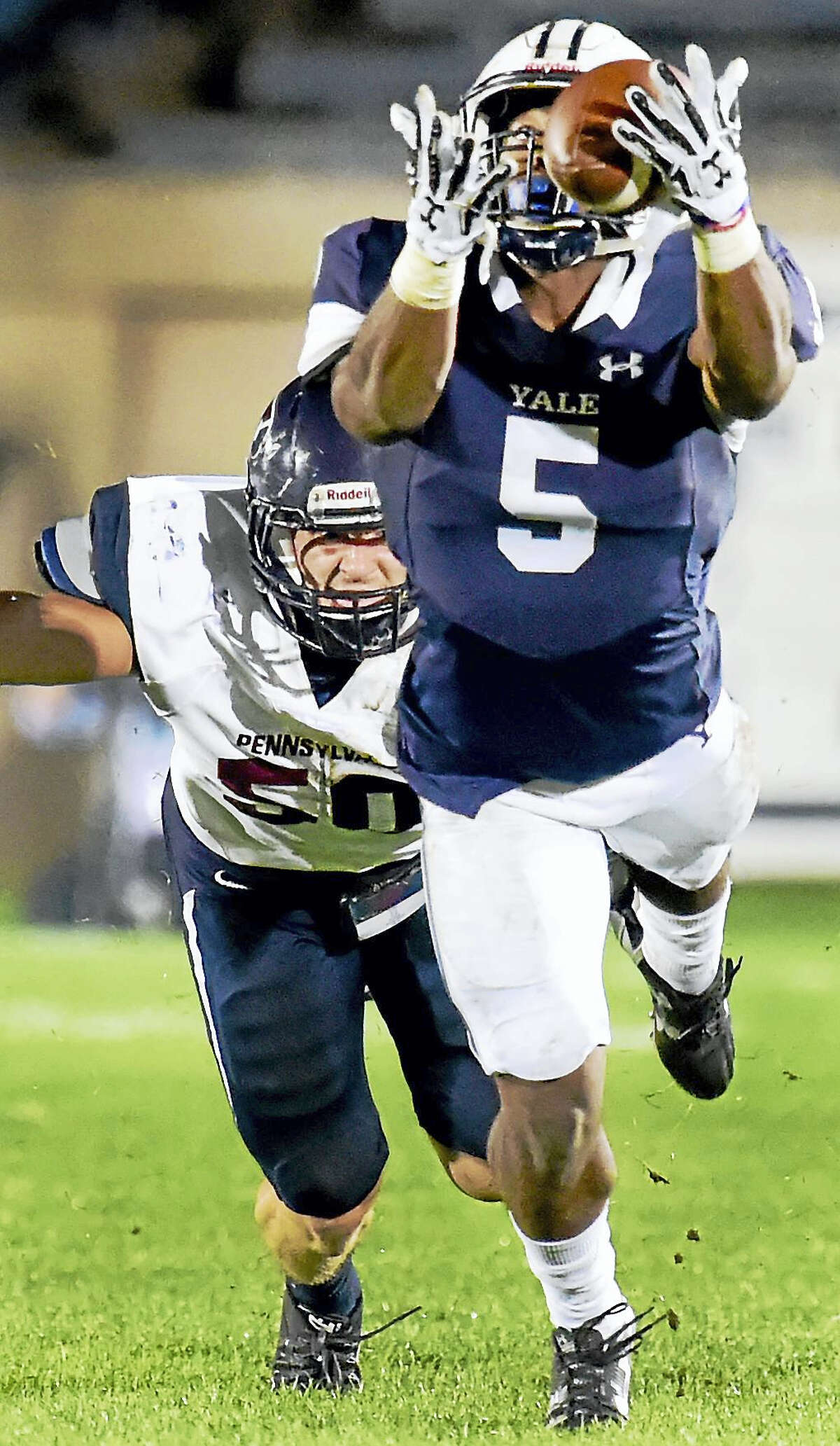 Yale's Alan Lamar of Yale reaches out for a pass against Penn defender Alex Weber in the first quarter on Friday.