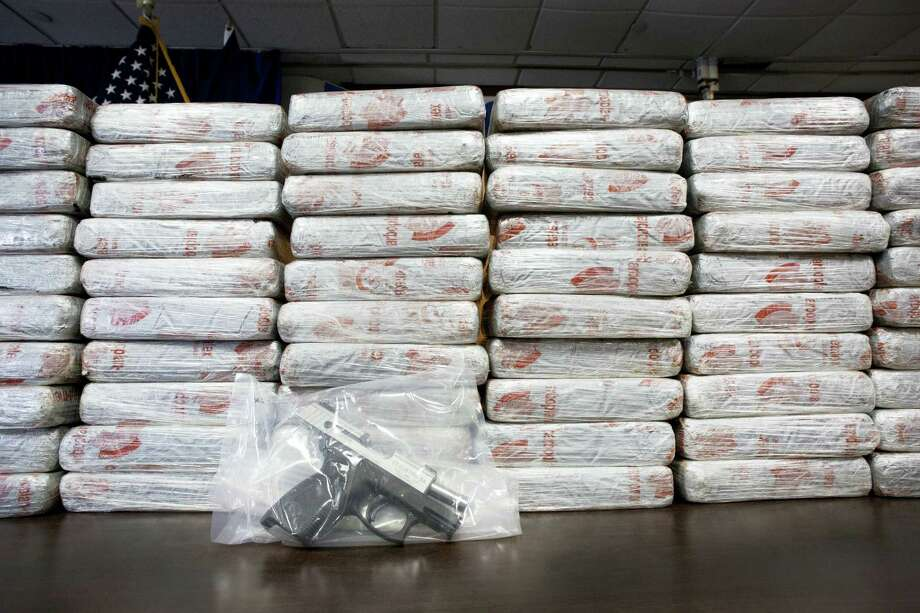 A firearm and 154 pounds of heroin worth at least $50 million are displayed at a Drug Enforcement Administration news conference on May 19, 2015 in New York. Photo: AP Photo/Mark Lennihan   / AP