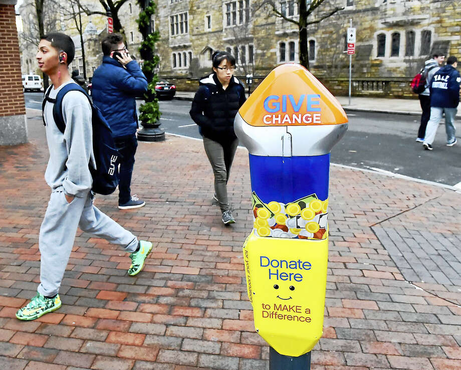 Pedestrians walk by a special parking meter Monday on York Street, designed for donating money to address panhandling and homelessness in New Haven. Photo: Peter Hvizdak — New Haven Register   / ©2016 Peter Hvizdak