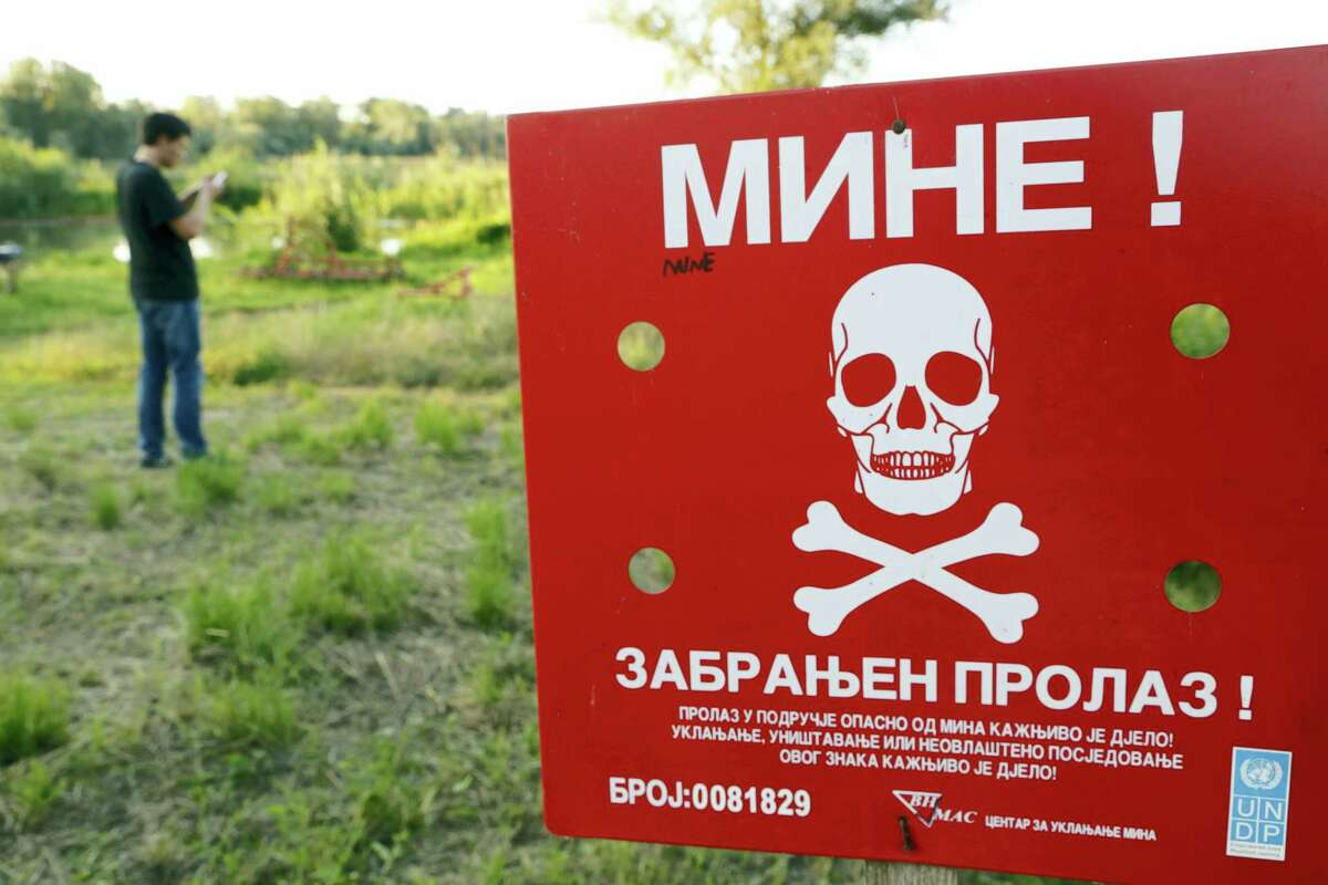 A Bosnian man plays the Pokemon game on his phone as he stands near a sign warning of a minefield, near the Bosnian town of Brcko, on Tuesday, July 19, 2016 . A non-governmental organization in Bosnia warns people not to walk into mine fields while playing the reality game Pokemon Go. Bosnia is one of the most mine-contested countries in the world. In New Jersey, U.S., also on Tuesday, a woman had to be rescued from a tree in which she got stuck while playing the game.