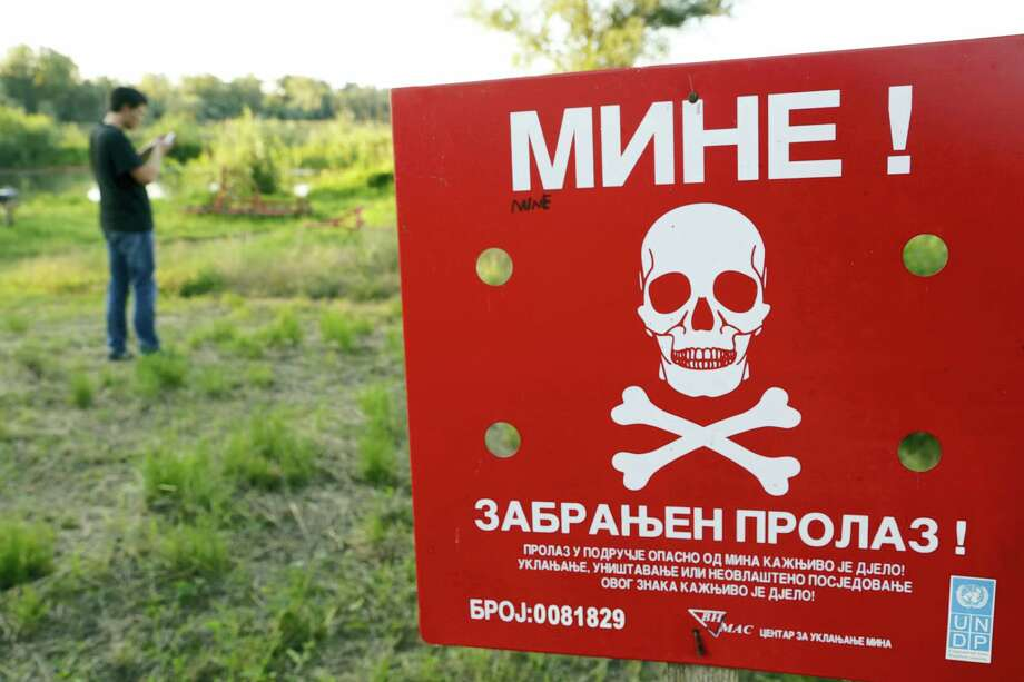 A Bosnian man plays the Pokemon game on his phone as he stands near a sign warning of a minefield, near the Bosnian town of Brcko, on Tuesday, July 19, 2016 . A non-governmental organization in Bosnia warns people not to walk into mine fields while playing the reality game Pokemon Go. Bosnia is one of the most mine-contested countries in the world. In New Jersey, U.S., also on Tuesday, a woman had to be rescued from a tree in which she got stuck while playing the game. Photo: AP Photo/Amel Emric    / Copyright 2016 The Associated Press. All rights reserved. This material may not be published, broadcast, rewritten or redistribu