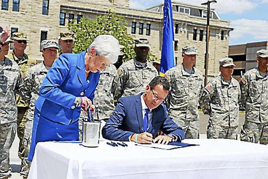 Gov. Dannel P. Malloy, right center, signing the bill with Lt. Gov. Nancy Wyman. Photo: Christine Stuart — CT News Junkie