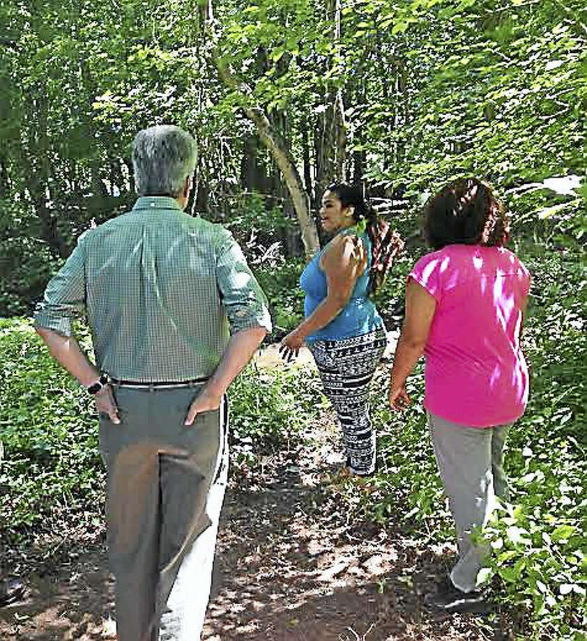 Students Yasdira Ra Perez and Kathiana Torres show New Haven Bird Club President Craig Repasz work they are doing near Wintergreen Brook. Photo: Brian Zahn - New Haven Register