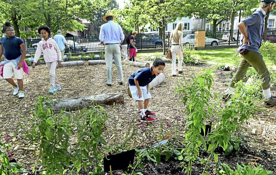 Takai Gonzales, 8, third from right, a Conte West Hills Magnet School third-grader, explores the school's new schoolyard habitat after an unveiling ceremony at the New Haven school Wednesday. Photo: Peter Hvizdak - New Haven Register   / ?2016 Peter Hvizdak