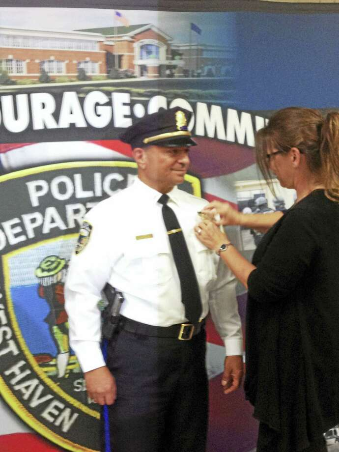 West Haven police Capt. Robert Proto has his new badge pinned on by his girlfriend, West Haven police Detective Tammy Murray. Photo: Mark Zaretsky — New Haven Register