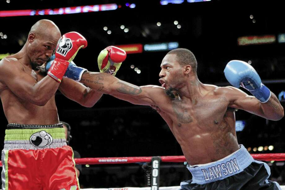 Bernard Hopkins, left, tries blocking a punch by Chad Dawson during the first round of their boxing match at the Staple Center on Saturday, Oct. 15, 2011, in Los Angeles. Dawson won by TKO in the second round after Hopkins wasn't able to continue due to a shoulder injury. (AP Photo/Richard Vogel) Photo: AP / AP2011