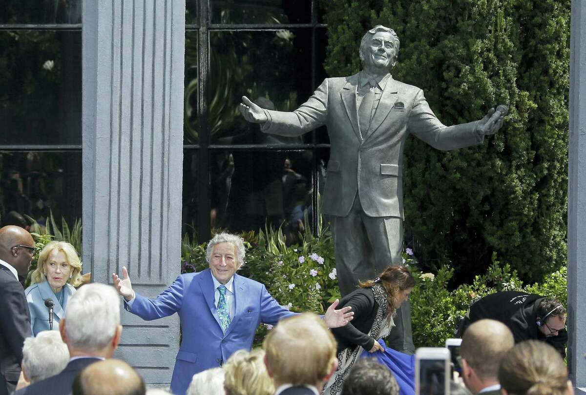 """Singer Tony Bennett gestures after his statue was unveiled outside the Fairmont Hotel Friday, Aug. 19, 2016, atop Nob Hill in San Francisco. Bennett arrived to a standing ovation and a jazz combo wishing him a very """"Happy Birthday."""" The music icon turned 90 on Aug. 3."""