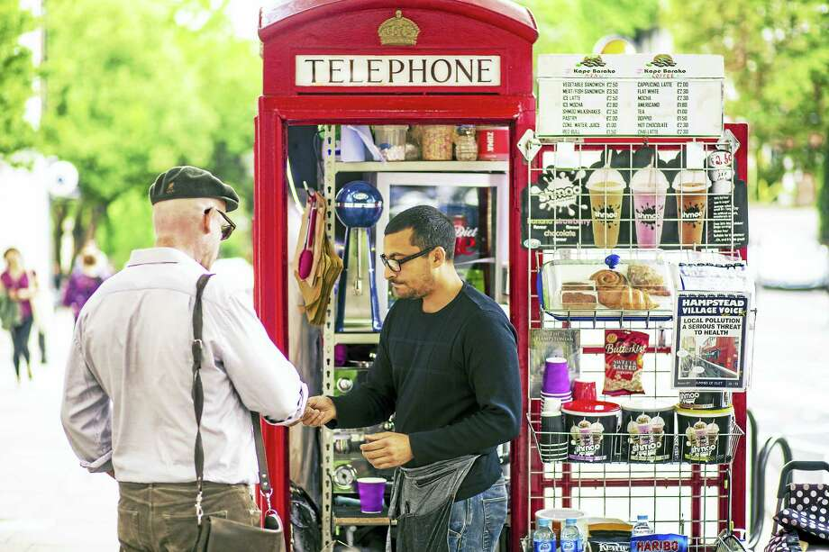 Umar Khalid, co-owner of the Kape Barako red telephone box coffee stall, serves a customer on Hampstead High Street in London. Photo: Miles Willis — Bloomberg Photo   / Bloomberg