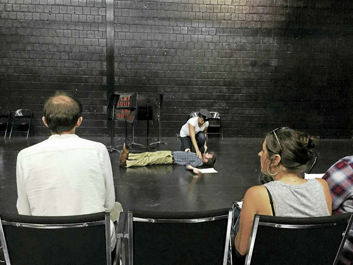LWT photo At rehearsal Thursday, Camelle Scott-Mujahid plays an officer standing over a body (Mike Merli) with Angela Clinton in the foreground with Aaron Jafferis.