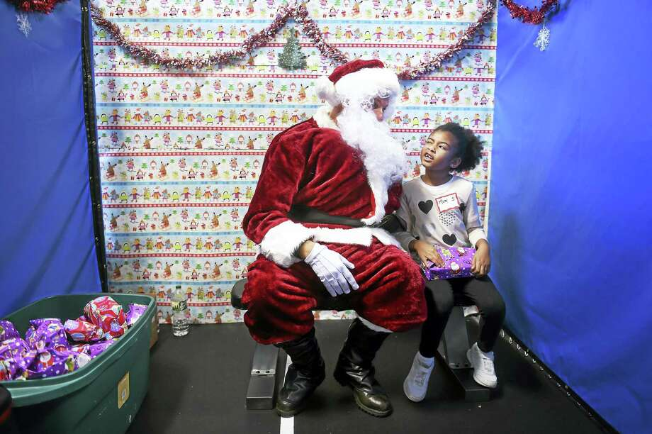 Santa Claus talks with Amelia Hamilton, 5, of Waterbury after giving her a present.. Photo: Arnold Gold-New Haven Register