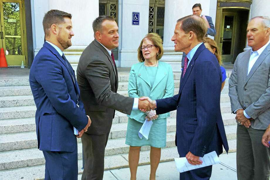 From left, Brett Eagleson stands next to his brother, Kyle, who shakes hands with U.S. Sen. Richard Blumenthal, D-Conn., before a press conference Tuesday outside U.S. District Court in New Haven. Photo: Esteban L. Hernandez — New Haven Register