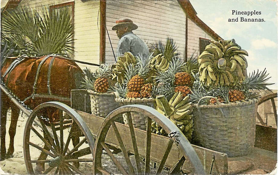 """A 1912 tinted black-and-white postcard of a banana and pineapple vendor is part of the new museum's collection. On the back of it is a handwritten note: """"don't forget / the place / Bradentown / Fla."""" Photo: Collection Of The Smithsonian National Museum Of African American History And Culture / Smithsonian's National Museum of African American History and Culture"""