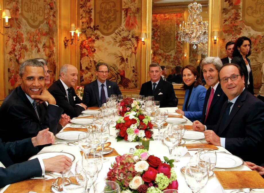 President Barack Obama, left, sits with French President Francois Hollande, right, as they have dinner at the Ambroisie restaurant in Paris, France, with Secretary of State John Kerry, 2nd right, French Minister for Ecology, Sustainable Development and Energy Segolene Royal, 3rd right, and French Foreign Minister, Laurent Fabius, 3rd left, Monday, Nov. 30, 2015. Obama is in France for a two-day visit as part of the COP21, the United Nations Climate Change conference. Other officials are : Translator, Thomas Ronkin, 2nd left, Charles Kupchan, top left, and French President Hollande's Military Chief of Staff General Benoit Puga, top right. (AP Photo/Thibault Camus, Pool) Photo: AP / AP POOL