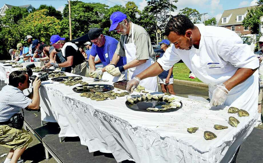 Jose Valdez of Queens, NY, a professional oyster shucker, right, competes in the Milford Oyster Festival shucking contest Saturday. Valdez, the winner of the contest, formerly worked at the Oyster Bar in Grand Central Station. Photo: Peter Hvizdak — New Haven Register   / ©2016 Peter Hvizdak