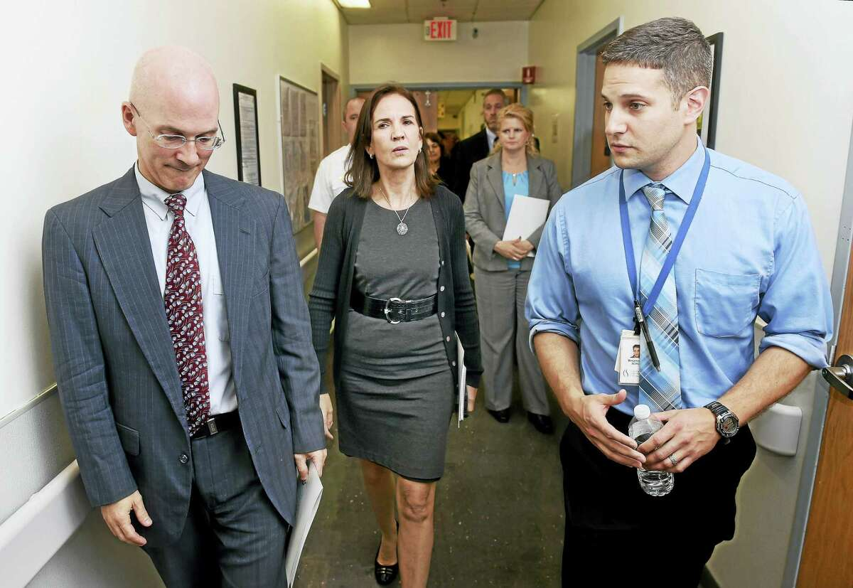 Assistant U.S. Attorney Robert Spector, l, U.S. Attorney Deirdre Daly, center, walk with Benjamin Metcalf, program director, South Central Rehabilitation Center, during a tour of the center in New Haven.