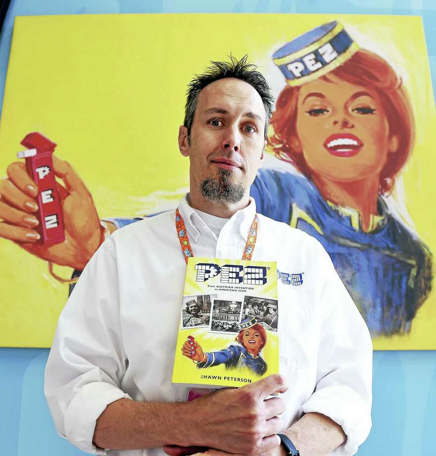 "Shawn Peterson, direct to consumer business manager at the Pez Visitor Center in Orange, is photographed with his book, ""PEZ: From Austrian Invention to American Icon."" Photo: Arnold Gold — New Haven Register"