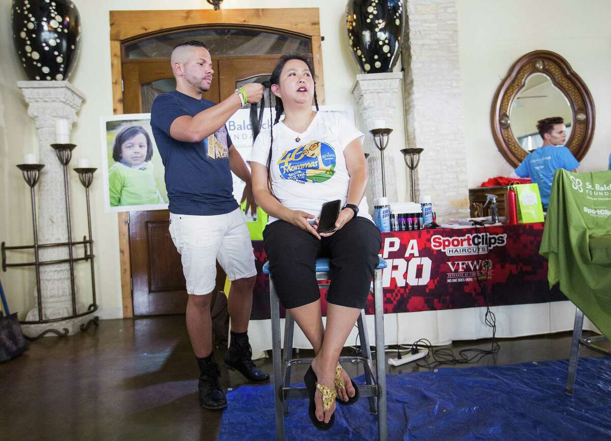 Rick Wright of Klepach Studio in San Antonio volunteers his time as a hairdresser as Judy Sanders gets her hair cut and shaved in memory of her son Alan for the 8th annual 46 Mommas Shave for the Brave, a St. Baldrick's Foundation event in Austin on July 23, 2017 in Austin, Texas.