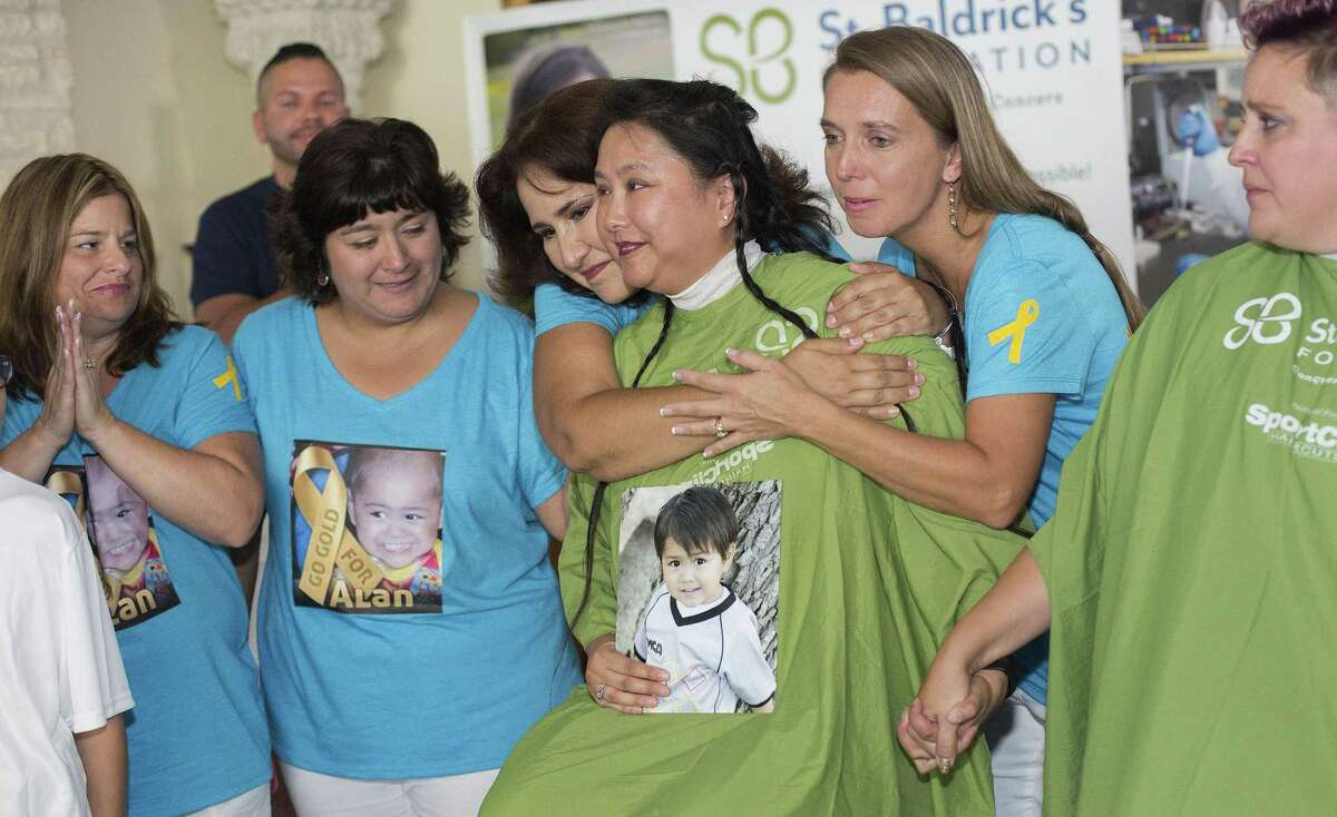 Judy Sanders, surrounds by friends who have been with her from the beginning, holds hands with fellow mom Lisa Sanders who together they will cut their hair for the 8th annual 46 Mommas Shave for the Brave, a St. Baldrick's Foundation event in Austin on July 23, 2017 in Austin, Texas.