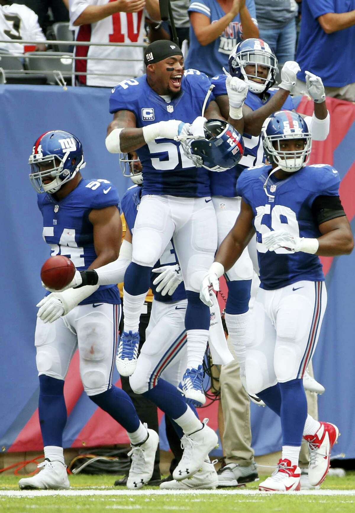Giants outside linebacker Jonathan Casillas (52) celebrates with teammate Janoris Jenkins and Devon Kennard (59) and Olivier Vernon (54) after Jenkins returned a blocked field goal for a touchdown on Sunday.