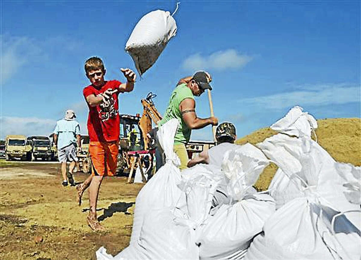 Young Dylan Heinan, among other volunteers, piles sandbags in an effort to stop flood waters from rising in Lake Arthur, La., Wednesday, Aug. 17, 2016.