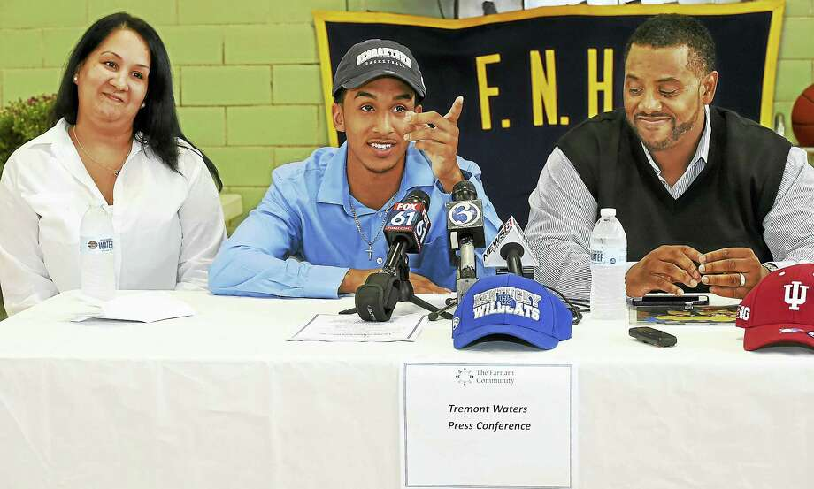 New Haven resident Tremont Waters, a senior point guard at Notre Dame-West Haven, with his parents, Vanessa and Edward, makes a verbal committment to play Division 1 college basketball at Georgetown University Wednesday at the Farnam Neighborhood House. Photo: CATHERINE AVALONE — NEW HAVEN REGISTER   / New Haven RegisterThe Middletown Press