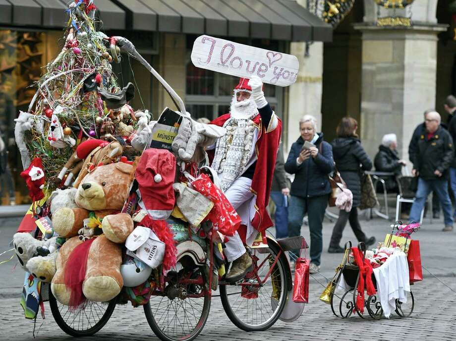 A street artist dressed as Santa Claus rides on a bicycle Thursday in the center of Muenster, Germany. Photo: Martin Meissner — The Associated Press   / Copyright 2016 The Associated Press. All rights reserved.