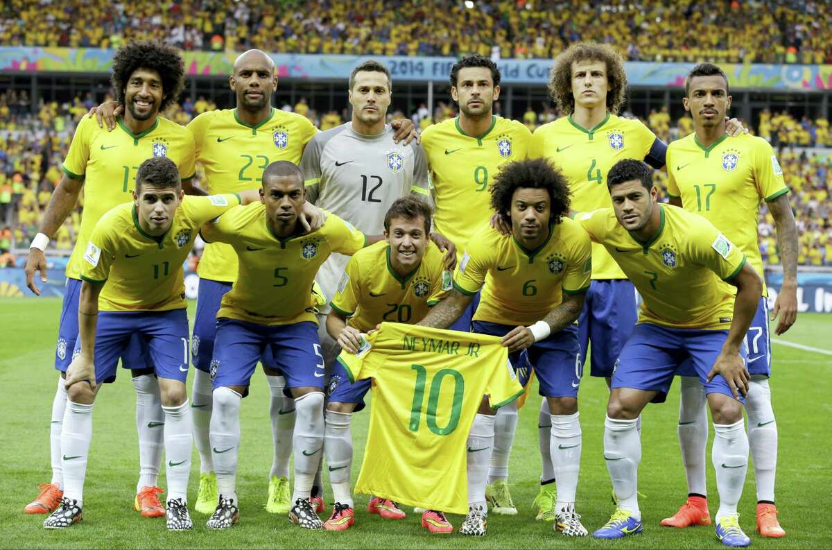 Brazil's national team holds up Neymar's jersey as they pose before their World Cup semifinal match with Germany in 2014 in Belo Horizonte, Brazil. Neymar missed the game after breaking a vertebrae.