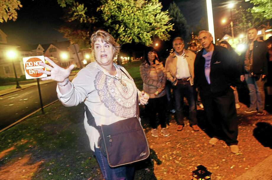 Cindy Wolfe Boynton, left, talks about the Smith Funeral Home and Rainbow Gardens Restaurant & Bar while leading a ghost walk through downtown Milford recently. Photo: Arnold Gold — New Haven Register