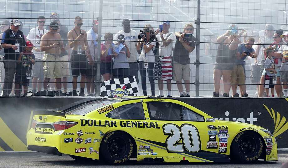 Matt Kenseth drives the checkered flag past fans after winning the New Hampshire 301 on Sunday in Loudon, N.H. Photo: Jim Cole — The Associated Press   / Copyright 2016 The Associated Press. All rights reserved. This material may not be published, broadcast, rewritten or redistribu