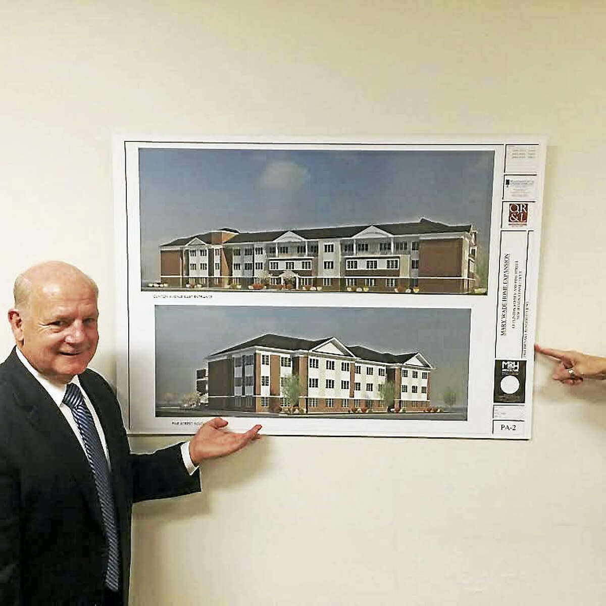 David Hunter, president and CEO of the Mary Wade Home, poses with a rendering of the new building proposed for 138 Clinton Ave.
