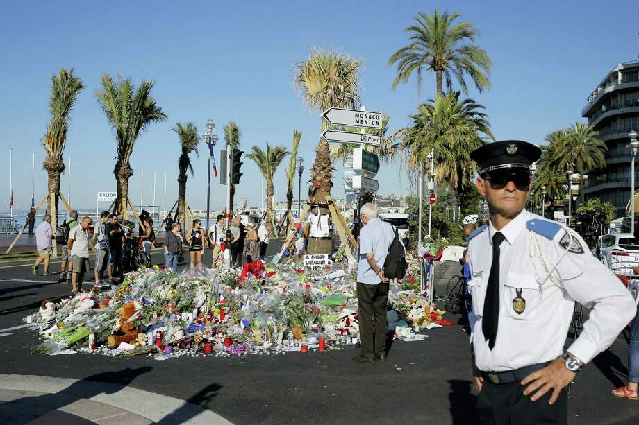 A police officer surveys people gathering around a floral tribute for the victims killed during a deadly attack, on the famed Boulevard des Anglais in Nice, southern France on Sunday, July 17, 2016. French authorities detained two more people Sunday in the investigation into the Bastille Day truck attack on the Mediterranean city of Nice that killed at least 84 people, as authorities try to determine whether the slain attacker was a committed religious extremist or just a very angry man. Photo: AP Photo/Laurent Cipriani   / AP