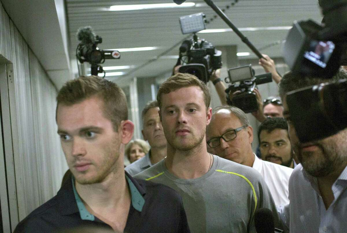 Journalists surround American Olympic swimmers Gunnar Bentz, left, and Jack Conger, center, as they leave the police station at Rio International airport early Thursday.