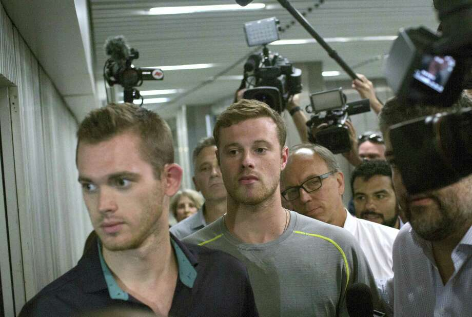 Journalists surround American Olympic swimmers Gunnar Bentz, left, and Jack Conger, center, as they leave the police station at Rio International airport early Thursday. Photo: Mauro Pimentel — The Associated Press   / Copyright 2016 The Associated Press. All rights reserved. This material may not be published, broadcast, rewritten or redistribu