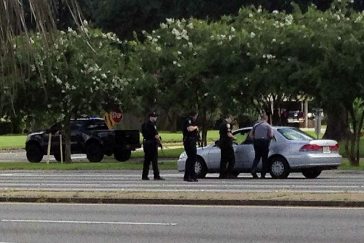 Authorities talk to the driver of a car near an area where several officers were shot while on duty less than a mile from police headquarters on Sunday, July 17, 2016 in Baton Rouge, La.