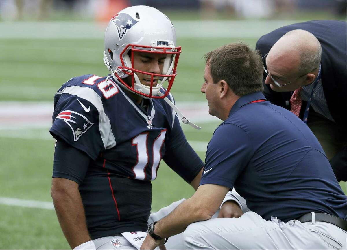 New England Patriots quarterback Jimmy Garoppolo receives attention after an injury during the first half of an NFL football game against the Miami Dolphins on Sept. 18, 2016 in Foxborough, Mass.