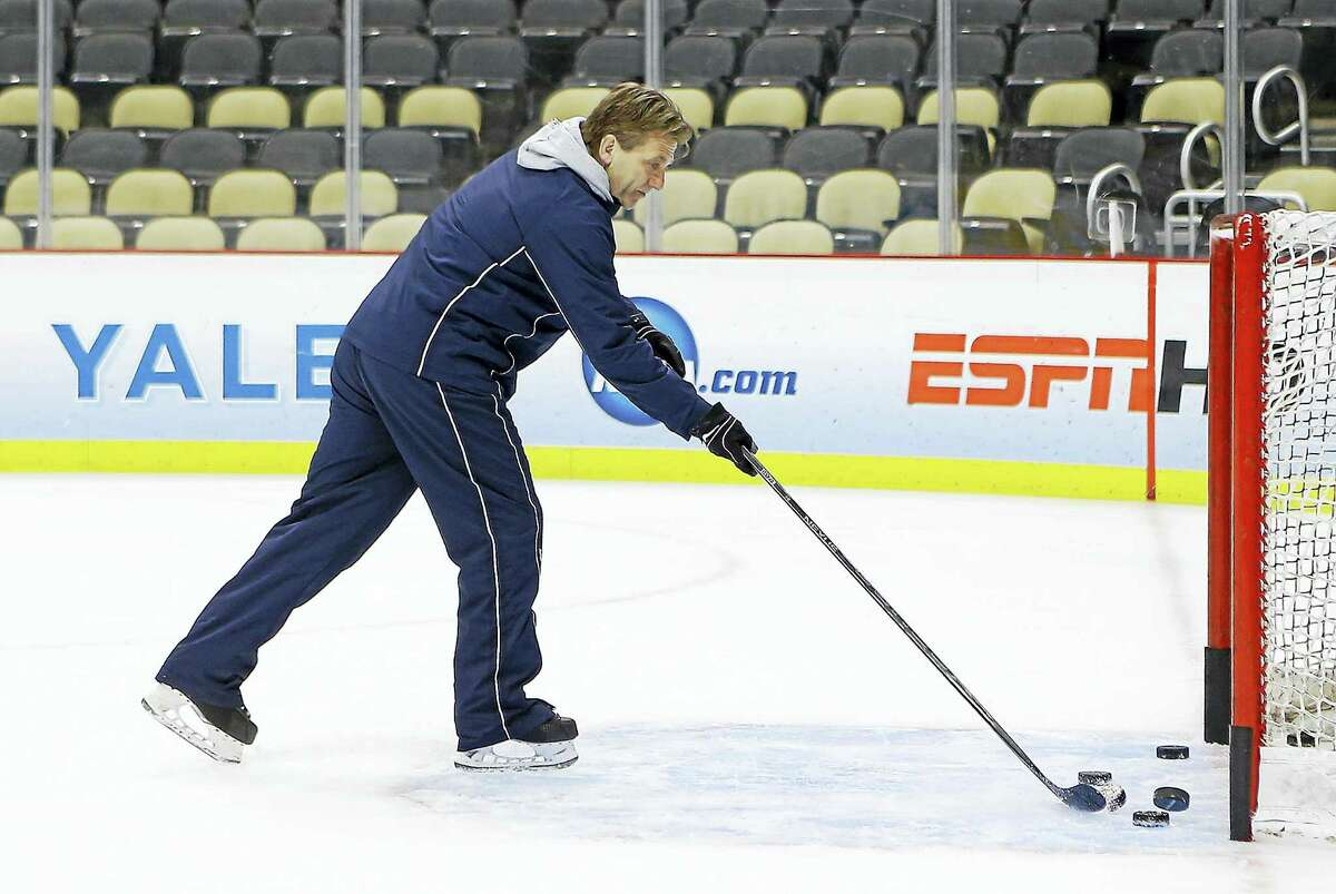 Yale coach Keith Allain puts pucks in a goal during NCAA college hockey practice at the Frozen Four, Friday, April 12, 2013, in Pittsburgh. Yale takes on Quinnipiac on the championship game on Saturday. (AP Photo/Keith Srakocic)