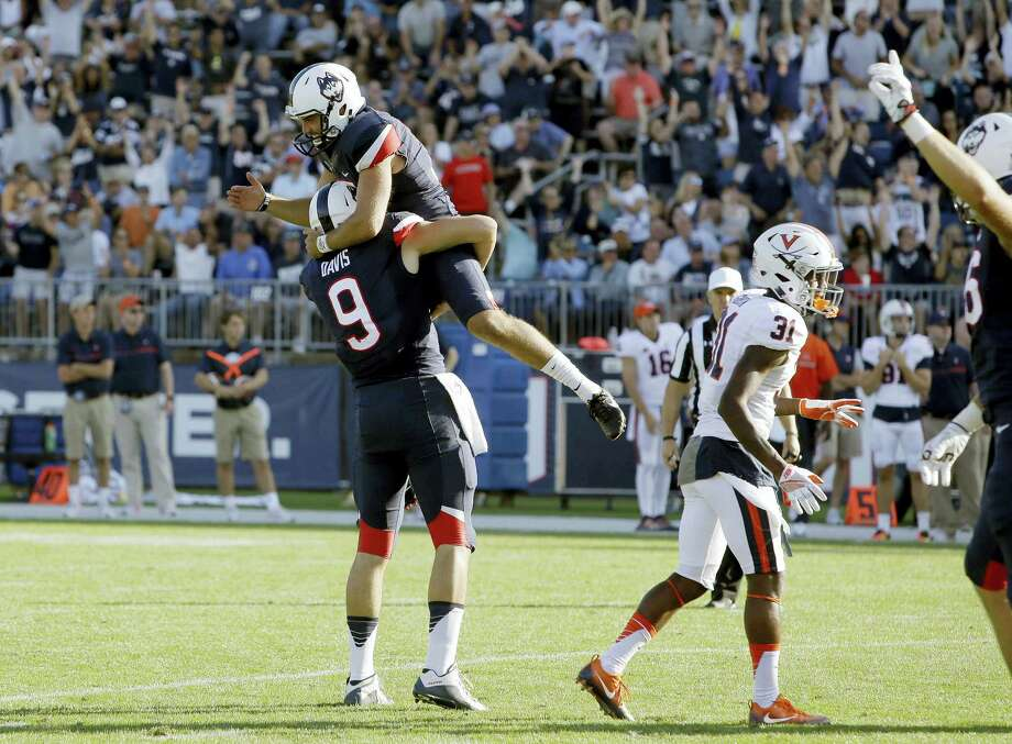 UConn kicker Bobby Puyol, top, celebrates his go-ahead field goal against Virginia with Tyler Davis on Saturday. Photo: Bill Sikes — The Associated Press   / AP