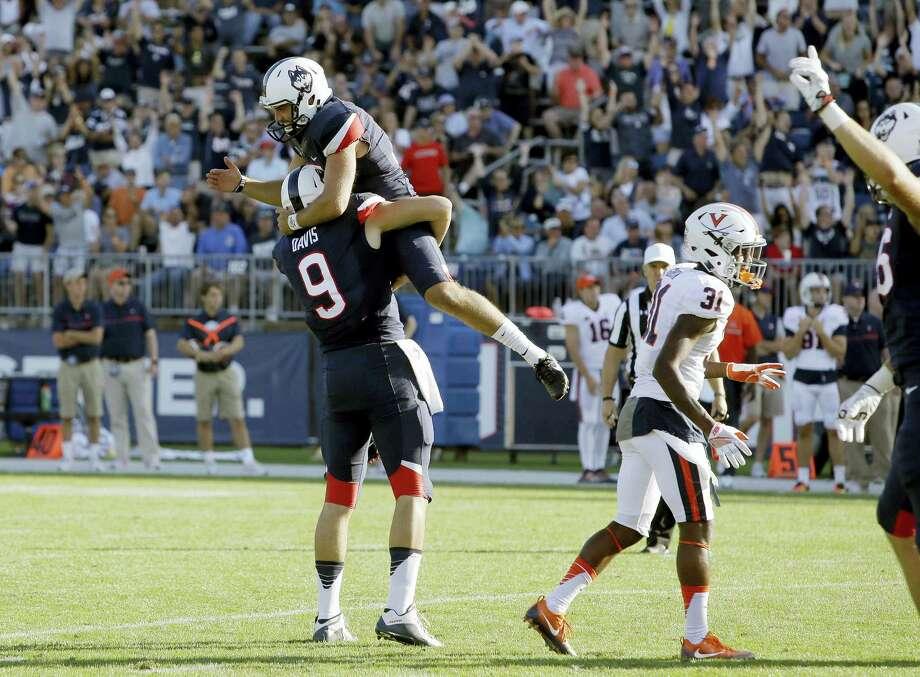 UConn kicker Bobby Puyol, top, celebrates his go-ahead field goal against Virginia with Tyler Davis on Saturday. Photo: Bill Sikes — The Associated Press   / AP