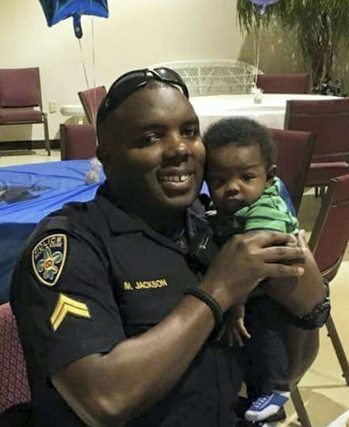 In this 2016 photo provided by Trenisha Jackson, her husband, Baton Rouge Police Officer Montrell Jackson, holds his son Mason at a Father's Day event for police officers in Baton Rouge, La. Montrell Jackson and two other Baton Rouge law enforcement officers investigating a report of a man with an assault rifle were killed Sunday, less than two weeks after a black man was fatally shot by police here in a confrontation that sparked nightly protests that reverberated nationwide. (Courtesy of Trenisha Jackson via AP)