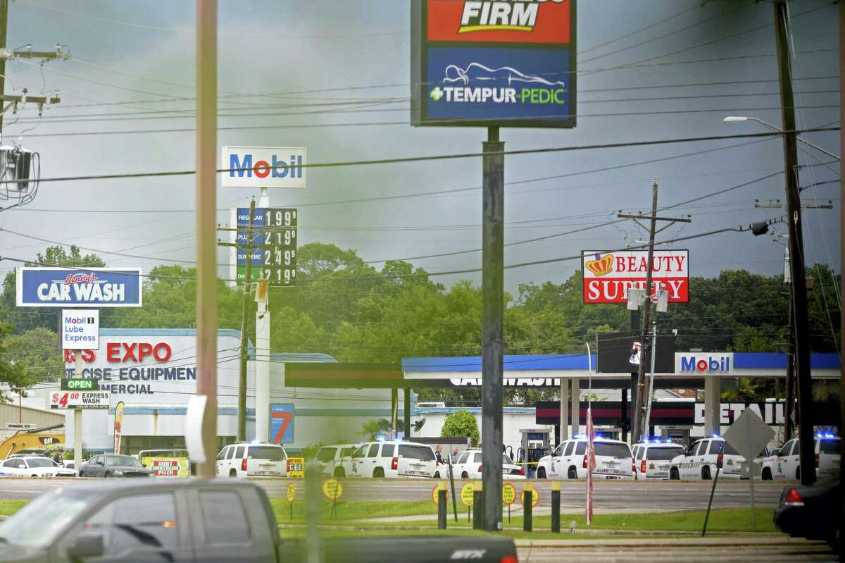 Law enforcement vehicles, many Louisiana State Police, line the side of Airline Highway near the scene the fatal shootings of police officers in Baton Rouge, La. Sunday, July 17, 2016. Multiple law enforcement officers were killed and wounded Sunday morning in a shooting near a gas station in Baton Rouge. (Hilary Scheinuk/The Advocate via AP)