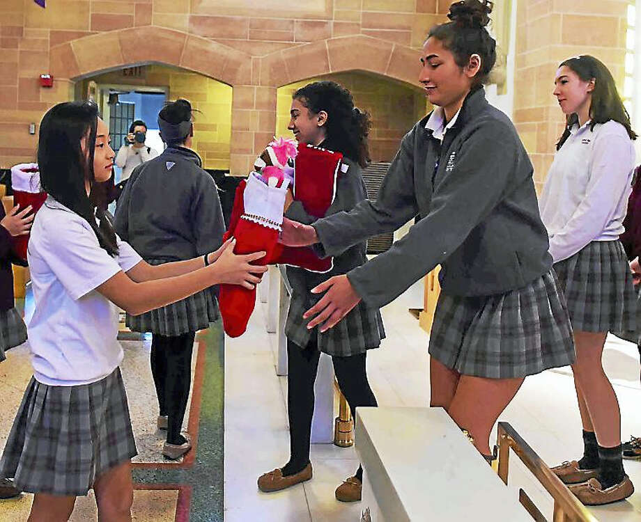 Sacred Heart Academy students finish their annual stocking drive Wednesday by placing filled stockings on the altar. The items will go to New Haven-area children in need. Photo: Peter Hvizdak — New Haven Register