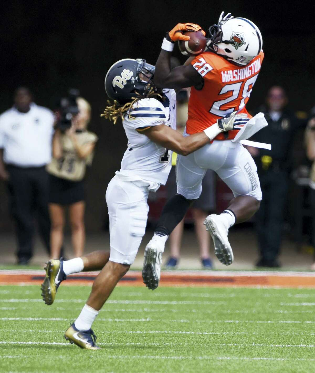 Oklahoma State wide receiver James Washington, right catches a pass while being tackled by Pittsburgh defensive back Avonte Maddox.