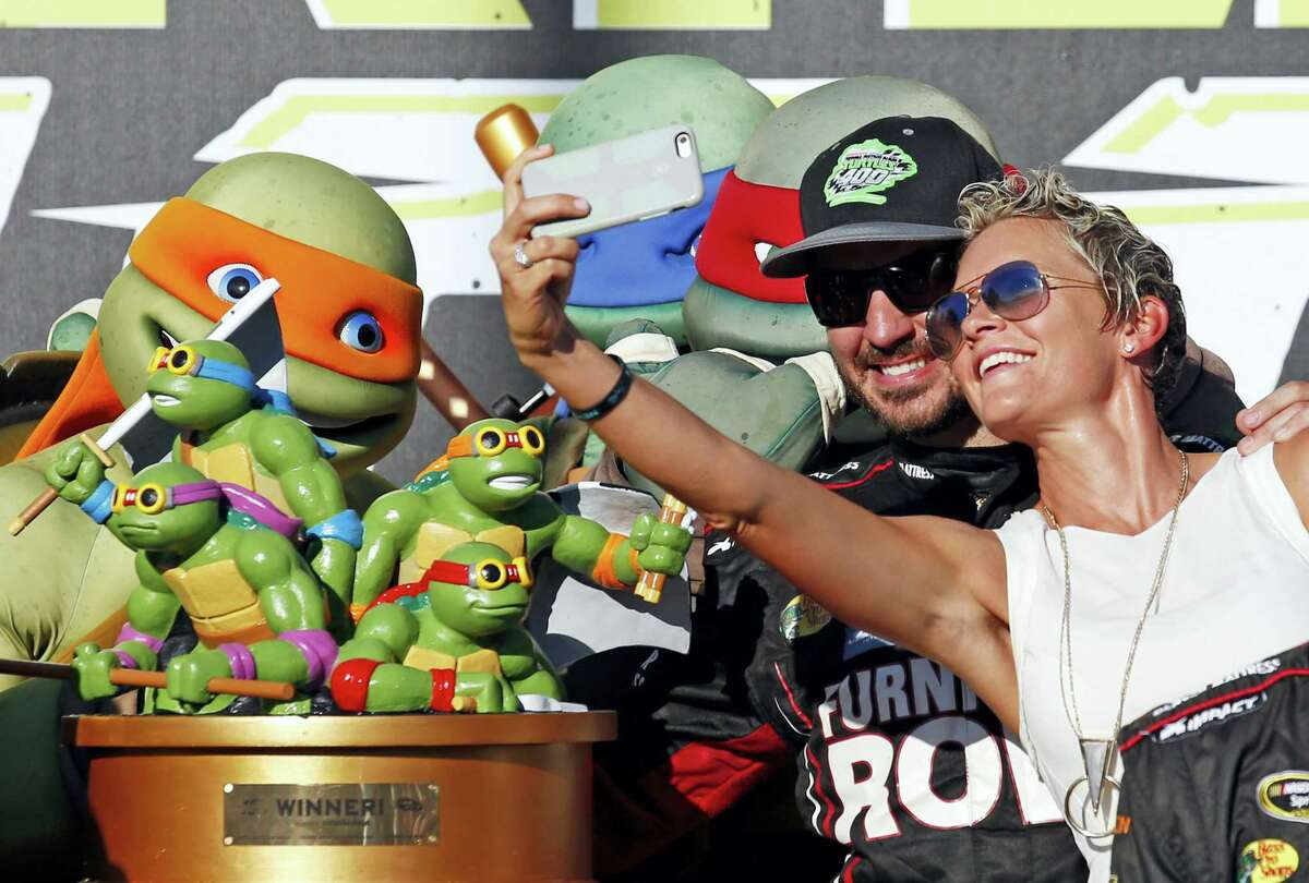 Martin Truex Jr., left, and his girlfriend, Sherry Pollex, pose for photos in Victory Lane after winning at Chicagoland Speedway on Sunday.