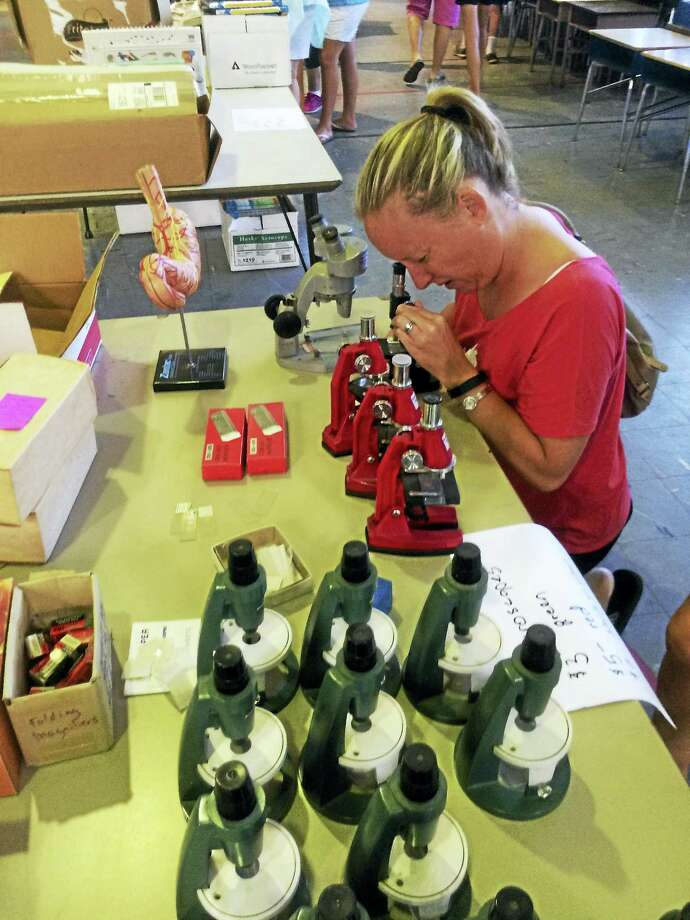 Cassandra Sherry checks out a microscope at the Academy Elementary School sale. Photo: Sarah Kyrcz Photo