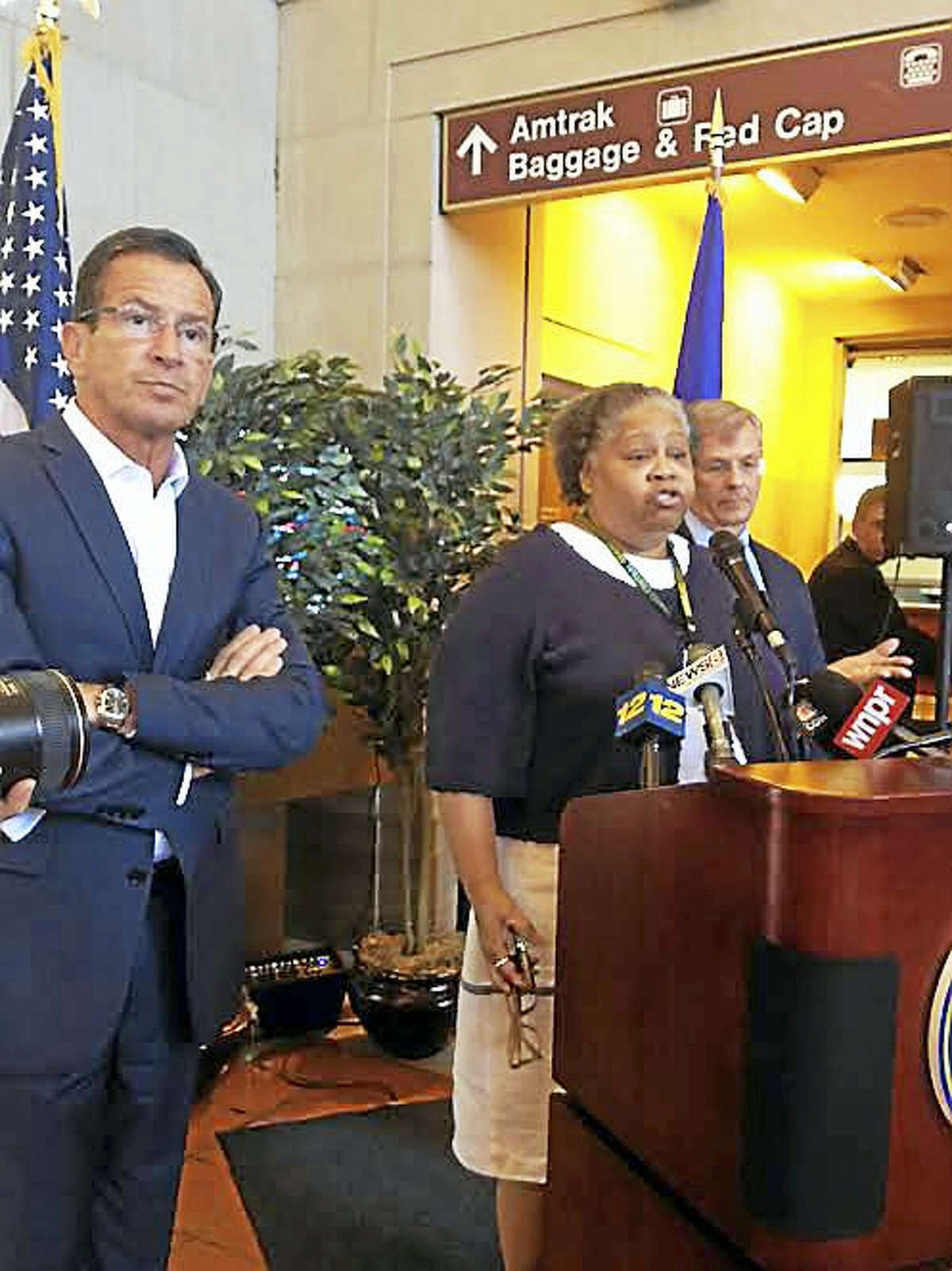 Gov. Dannel P. Malloy, left. Is joined by a Metro North employee and state Department of Transportation Commissioner James Redeker at Union Station in New Haven Thursday.