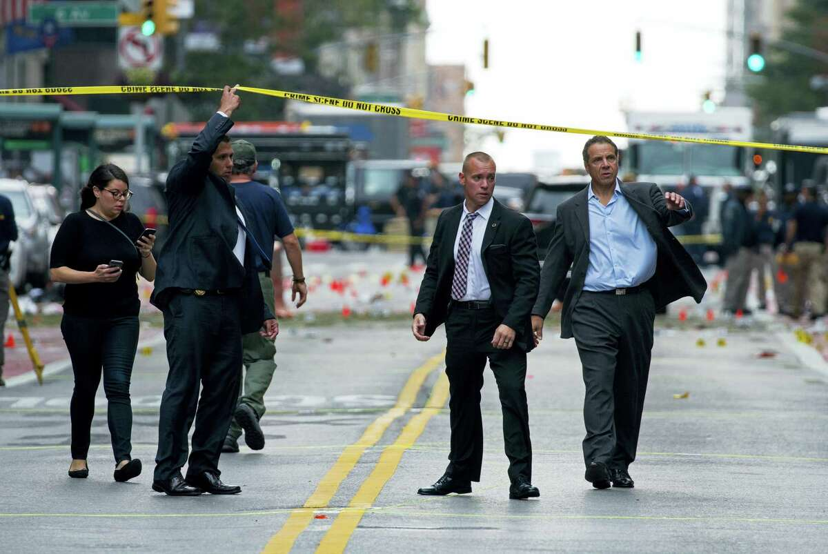 New York Gov. Andrew Cuomo, right, walks from the scene of an explosion in Manhattan's Chelsea neighborhood in New York on Sept. 18, 2016, after an incident that injured passers-by Saturday night.