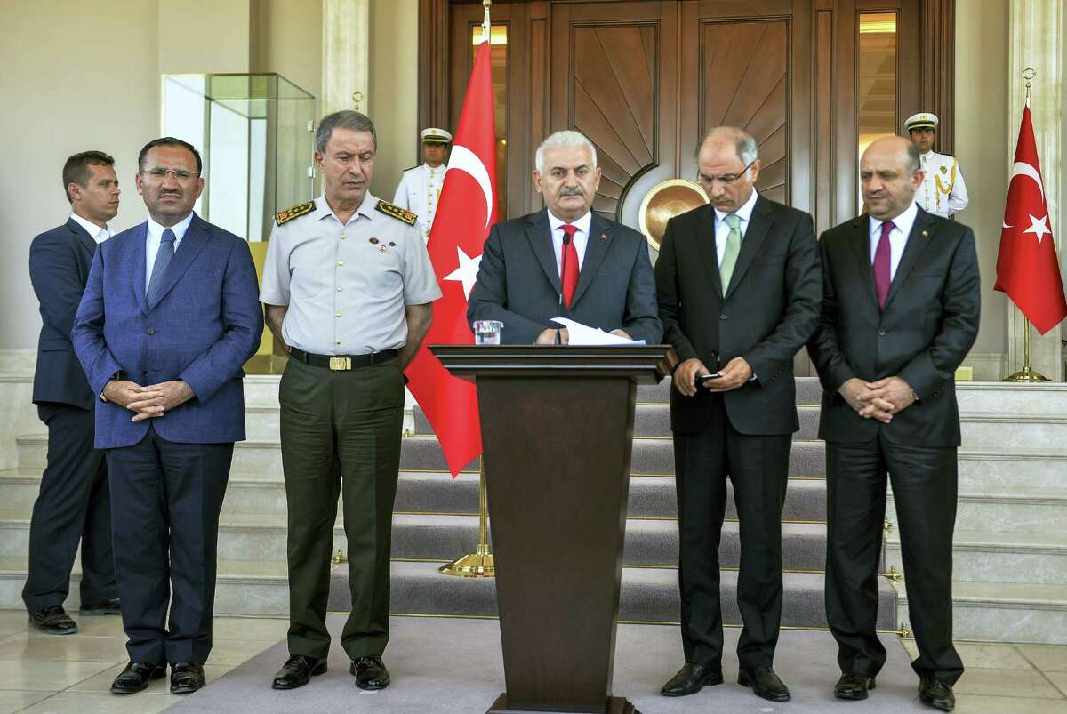 """Turkey's Prime Minister Binali Yildirim, center, Chief of Staff Gen. Hulusi Akar, center left, Justice Minister Bekir Bozdag, left, Interior Minister Efkan Ala, second right, and Defense Minister Fikri Isik attend a press conference in Ankara, Turkey, Saturday, July 16, 2016. Forces loyal to Turkey's President Recep Tayyip Erdogan quashed a coup attempt in a night of explosions, air battles and gunfire that left dozens dead Saturday. Authorities arrested thousands of people as President Recep Tayyip Erdogan vowed those responsible """"will pay a heavy price for their treason."""""""