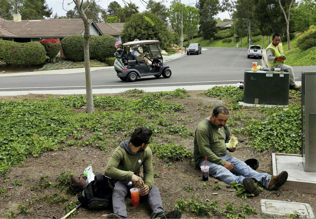 In this May 4, 2016 photo, Duncan Wallace drives a golf cart from his house to his golf club as a group of landscape workers take a break in Vista, Calif. Income inequality has surged near levels last seen before the Great Depression.