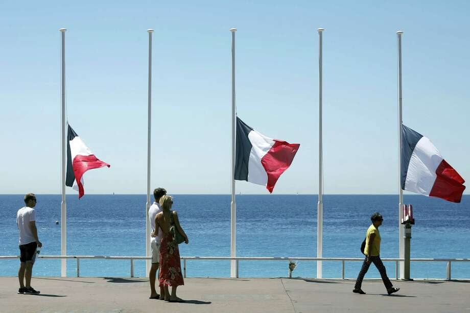 People stroll on the Promenade des Anglais with the French flag at half mast,  near the scene of a truck attack in Nice, southern France, Saturday, July 16, 2016. The man responsible for turning a night of celebration into one of carnage in the seaside city of Nice was a petty criminal who hadn't been on the radar of French intelligence services before the attack. Photo: AP Photo/Laurent Cipriani    / AP